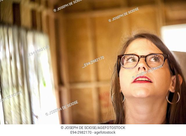 A 26 year old woman wearing large glasses looking up, lips parted
