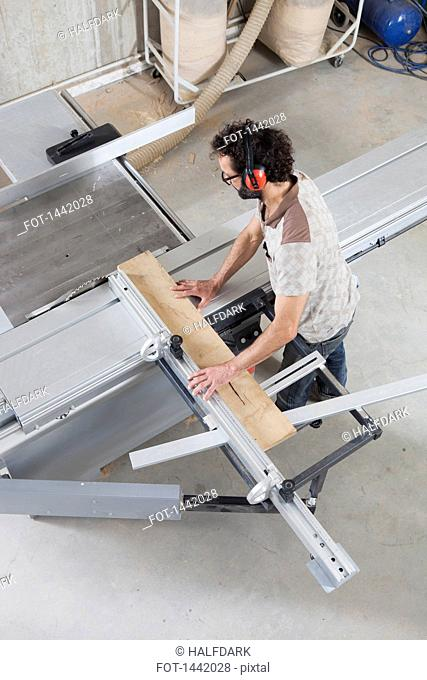 High angle view of carpenter using a sliding table saw in workshop