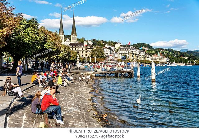 Tourists relax at the Schweizerhofquai lakeshore of Lake Lucerne in Summer, Lucerne, Switzerland