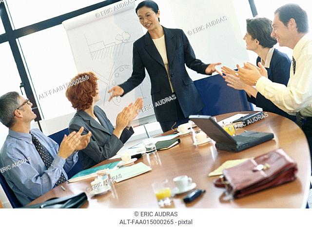 Business meeting, woman standing while colleagues clap
