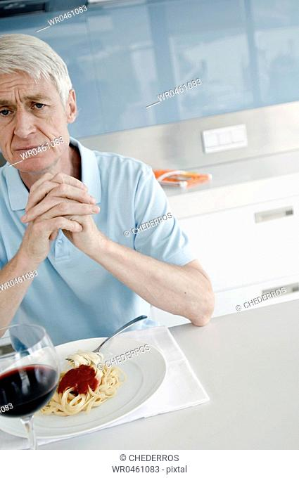 Portrait of a senior man sitting at the kitchen counter with his hands clasped