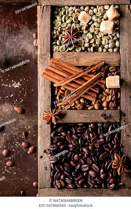 Green and brown decaf unroasted and black roasted coffee beans with spices and sugar cubes in old wooden box over dark brown textured background