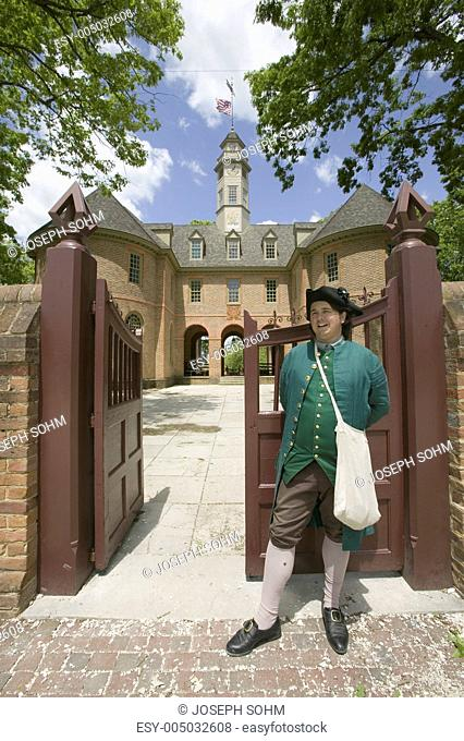 18th Century reenactor standing at front gate of the Capitol Building of Colonial Williamsburg, Virginia. In this building Patrick Henry, George Washington