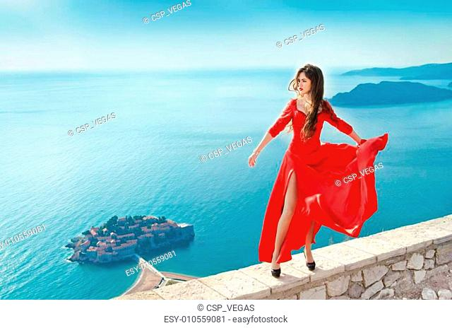 Beautiful Girl in blowing red dress Flying. Fashion gorgeous mod