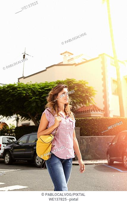 Confident woman walking down the street and looking away - focus on foreground