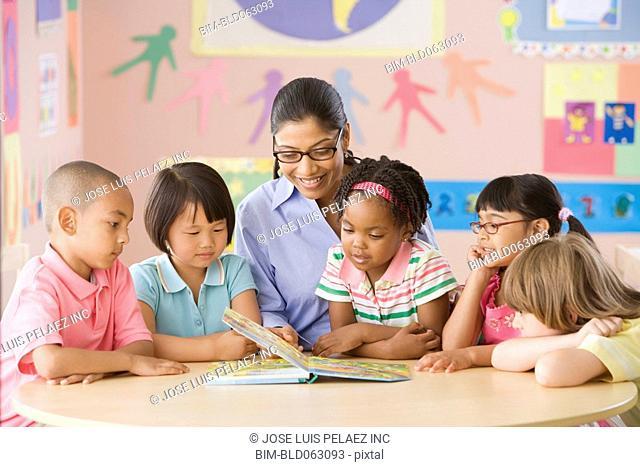 Multi-ethnic school children listening to teacher read book