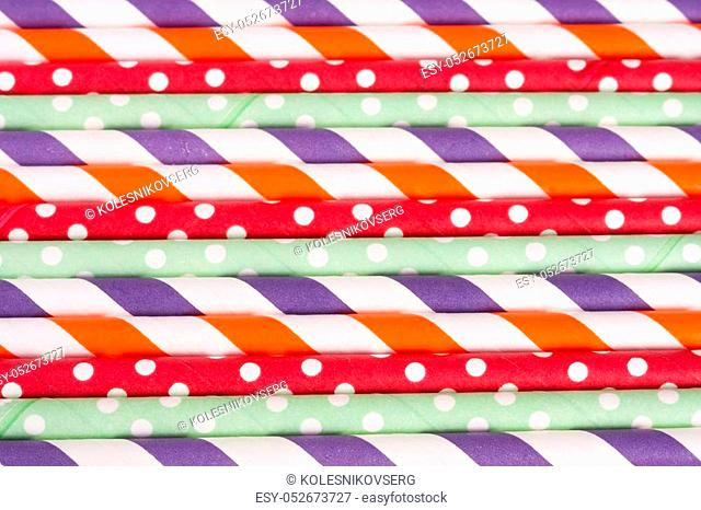 Colorful drinking striped straws as a background
