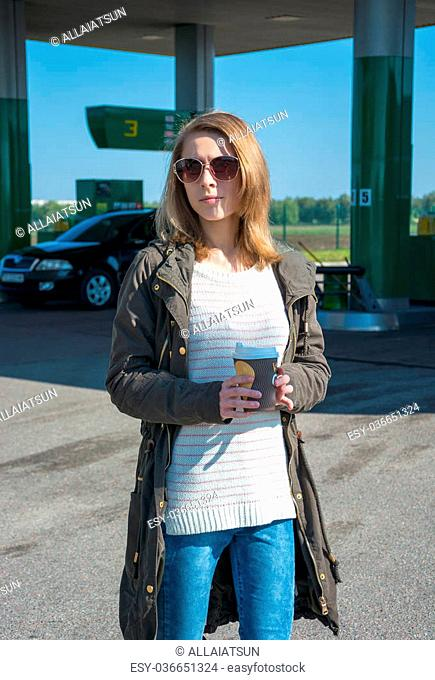 Girl in a jacket with a cup of coffee at a gas station