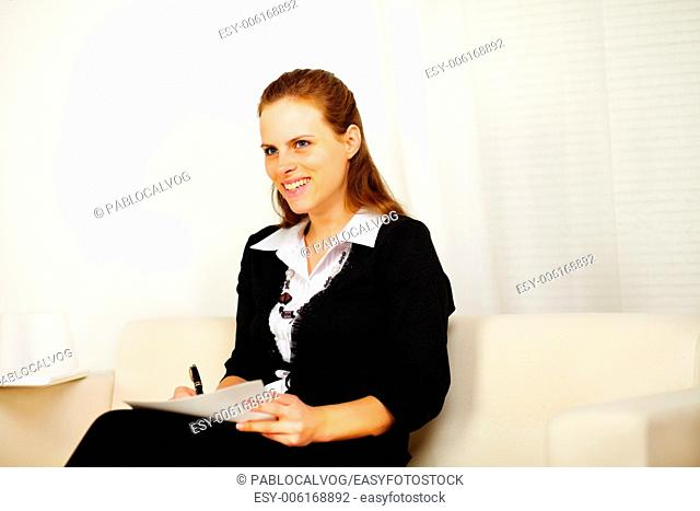 Portrait of a pretty business woman smiling and working with a laptop and documents