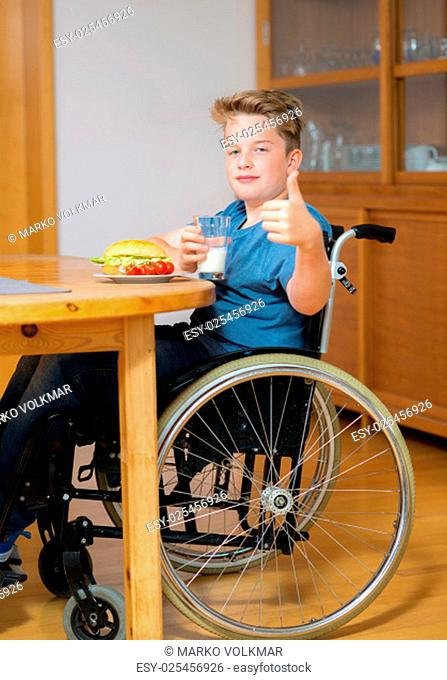 disabled boy with thumb up in wheelchair is eating in the living room