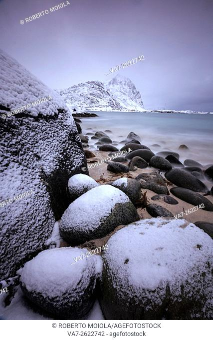 Snow covered rocks on the beach modeled by the wind surround the icy sea Pollen Vareid Flakstad Lofoten Islands Norway Europe