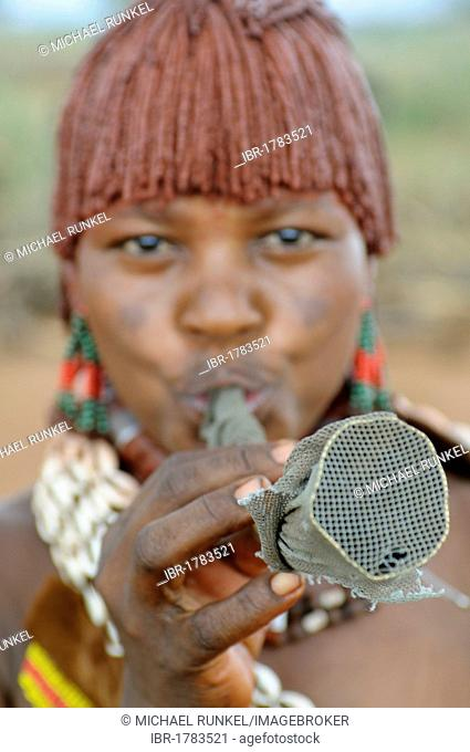 Young woman from the Hamar tribe blowing a horn in order to gain attention during the bull-leaping ceremony, an initiation rite, southern Omo Valley, Ethiopia