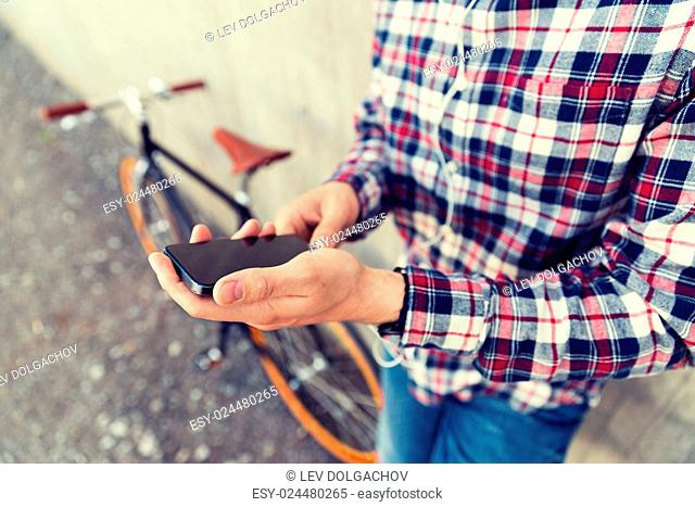 people, technology, leisure, advertisement and lifestyle - close up of young hipster man in earphones with fixed gear bike listening to music and showing...