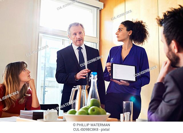 Businesswoman and male colleague giving presentation on digital tablet during office meeting