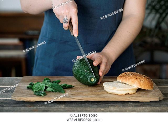 Woman preparing vegan burger, slicing avocado