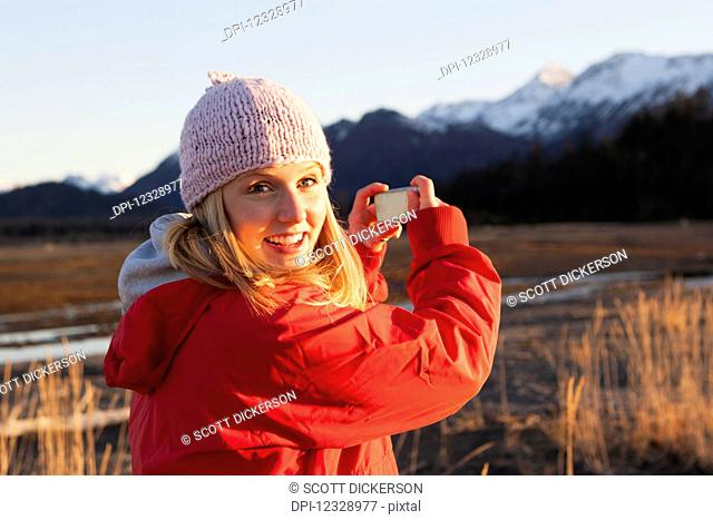 A Young Woman Takes A Picture Of The Kenai Mountains In Kachemak Bay State Park; Alaska, United States Of America