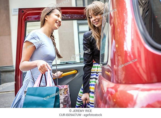 Young women getting into taxicab, carrying shopping bags