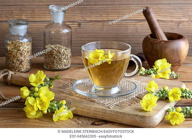 A cup of herbal tea with fresh mullein flowers on a rustic background