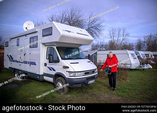 31 January 2020, Mecklenburg-Western Pomerania, Rerik: Jochen Klopp from Neustadt in Holstein is installing a power connection in front of his motorhome at the...