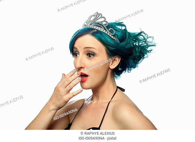 Young woman with green hair wearing tiara and looking surprised