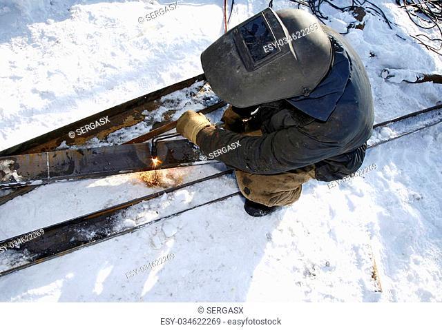 Industrial worker uses an acetylene torch in winter outdoor