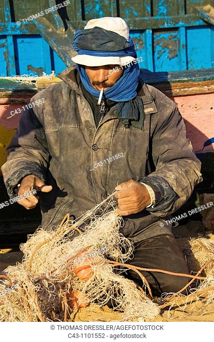 Morocco - Fisherman repairing a net at the sandy beach of Oualidia, a seaside town and fishing port at the Atlantic Ocean south of El Jadida