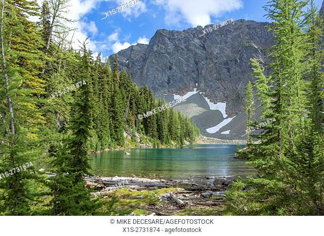 Old and new growth Evergreen trees frame pristine Blue Lake in the North Cascade range