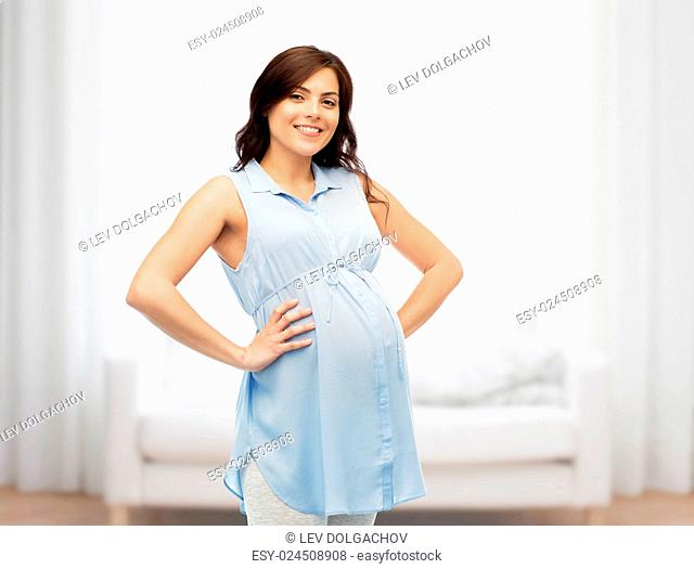 pregnancy, motherhood, people and expectation concept - happy pregnant woman touching her big belly over home room background