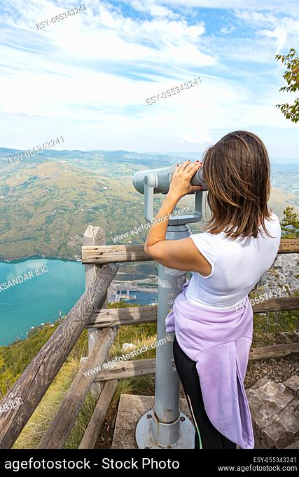 Woman hiker at mountain viewpoint looking throgh touristic telescope at the lake and canyon in the distance