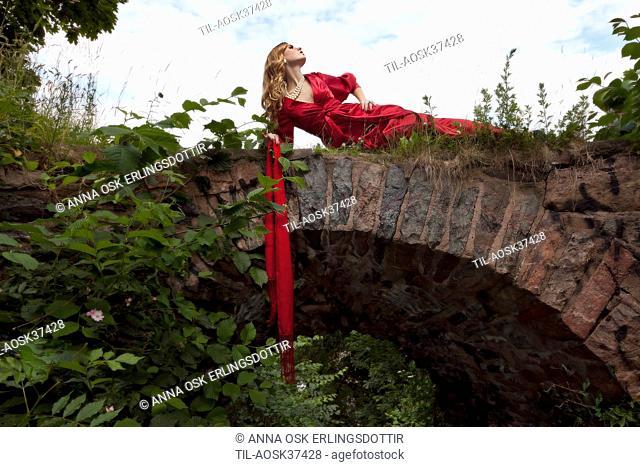 Lone female figure wearing red silk dress lying on bridge