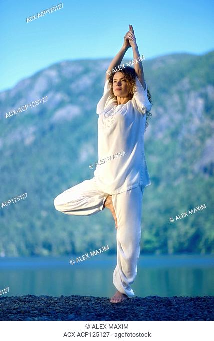 Young woman practicing yoga outdoors in the nature during morning sunrise at a lake. Vriksasana or Vrksasana, standing tree pose
