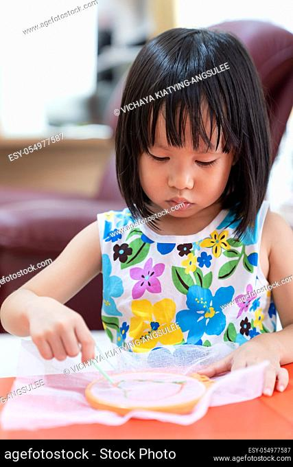 Asian girl child sewing in living room at home as home schooling while city lockdown because of covid-19 pandemic across the world