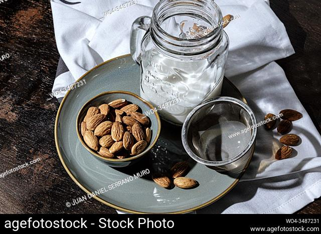 Almond vegan milk just strained into a glass jar, next to a bowl of raw almonds and a metal strainer