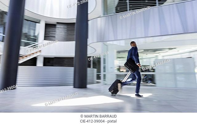 Businessman rushing, pulling suitcase in modern office lobby