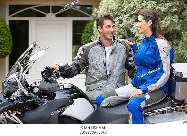 Smiling couple on motorcycle in driveway