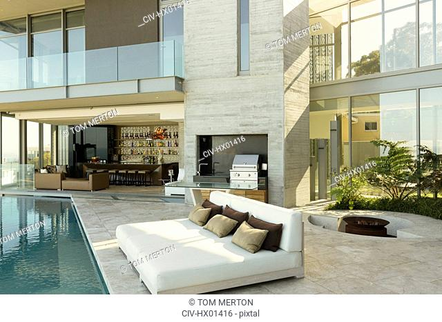 Luxury home showcase exterior patio with chaise lounges at poolside