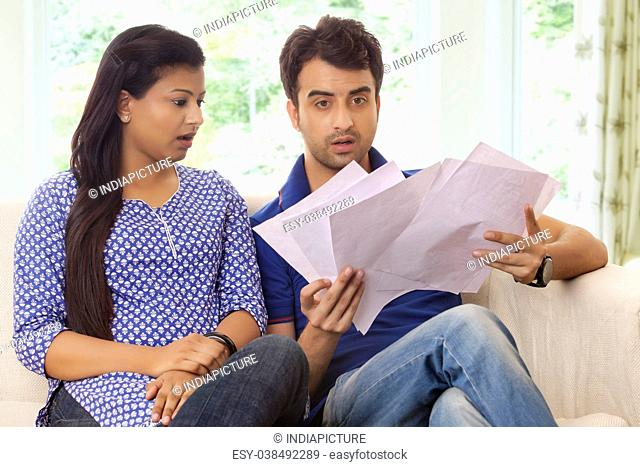 Couple surprised looking at bills