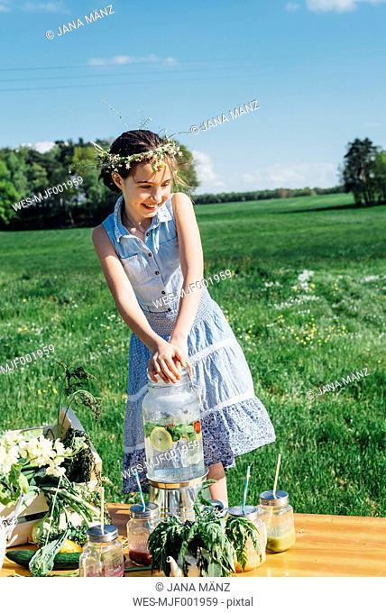 Smiling girl wearing flower wreath on meadow