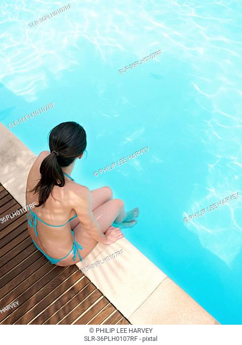 Woman dangling her feet in pool