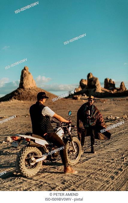 Motorcyclist friends talking on dirt track, Trona Pinnacles, California, US
