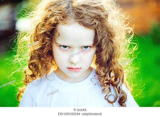 Emotional child with angry expression on face