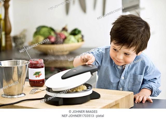 Boy checking waffle-iron