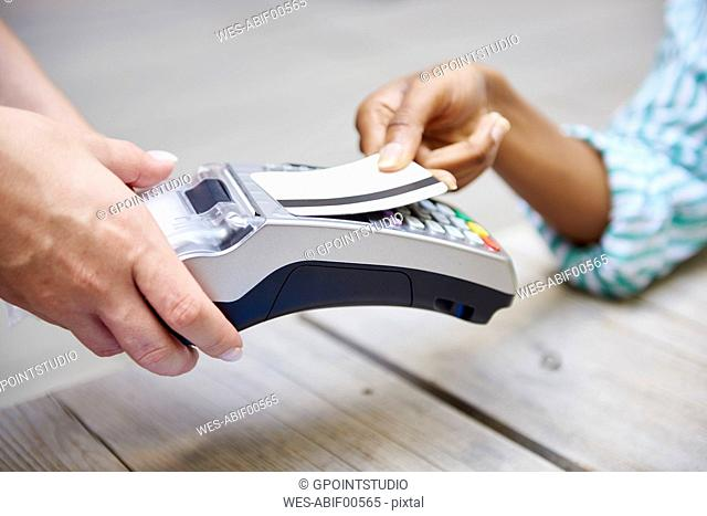 Woman paying by credit card at pavement cafe, close-up