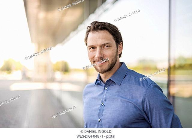 Portrait of smiling businessman outdoors