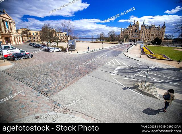 31 March 2020, Mecklenburg-Western Pomerania, Schwerin: The Old Garden in front of Schwerin Castle in the centre of the state capital is almost deserted