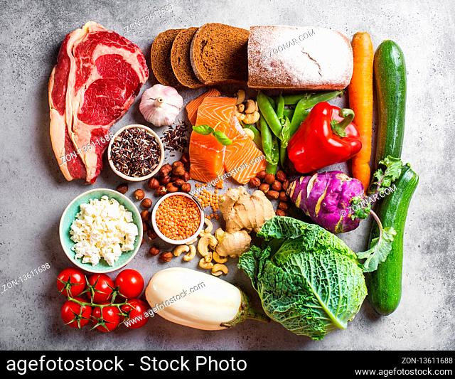 Assortment of healthy balanced food composition: meat, fish, vegetables, bread, cereals, beans, stone background. Raw ingredients for cooking healthy meal