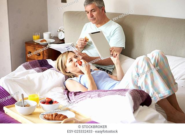 Couple Eating Breakfast In Bed With Paper And Digital Tablet