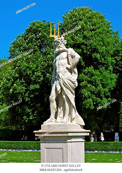 Neptune sculpture made of marble from Sterzing in garden terraces of Nymphenburg Palace, flowering chestnut trees