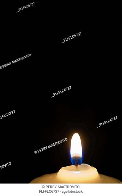 Close-up of a White Candle with Flame against a Black Background, Studio Composition