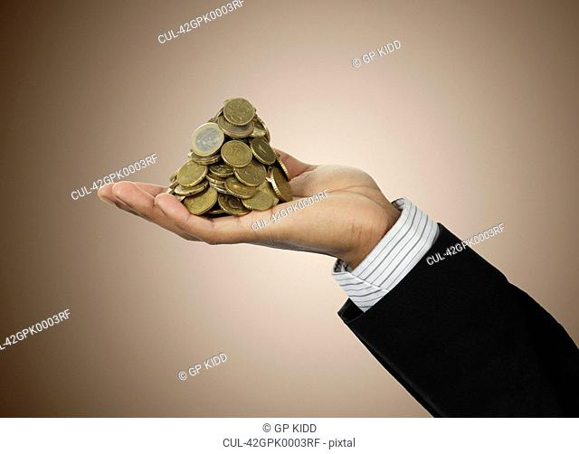 Businessman holding stack of Euro coins